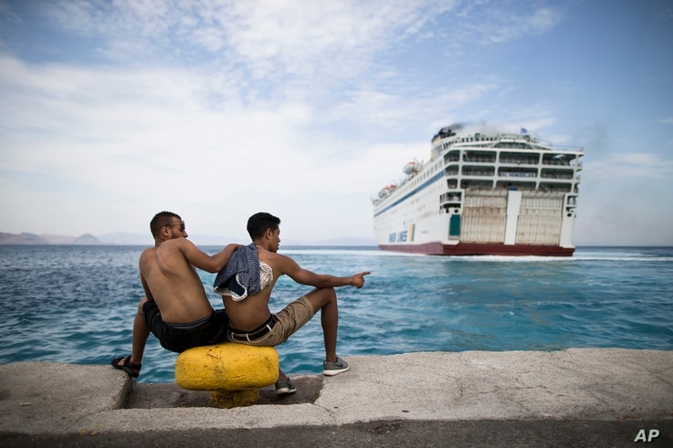 Two migrants look toward a giant passenger ferry while it arrives at the Greek holiday island of Kos, to provide temporary accommodation for some thousands of refugees sleeping rough after crossing clandestinely from Turkey in flimsy boats, Aug. 14, ...
