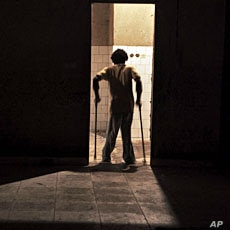 A November 2011 file photo shows a youth suffering from polio walking through a doorway at the Stand Proud compound in Kinshasa, Republic of Congo