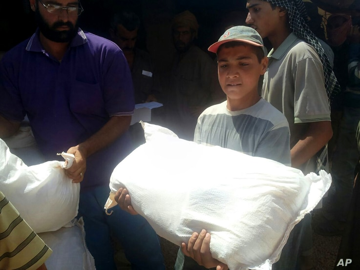 FILE - A boy holds a sack of food aid after aid agencies dropped via crane food across the Jordan-Syria border to community leaders charged with distributing equitably the supplies to the 64,000-person refugee camp called Ruqban.