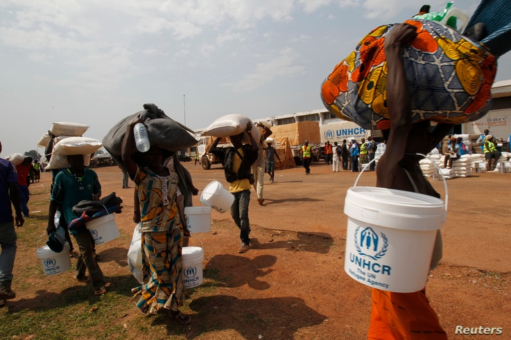 FILE - People displaced by the recent unrest, collect food distributed by aid agencies at an IDP camp at the Mpoko international airport of Bangui, Feb. 12, 2014.