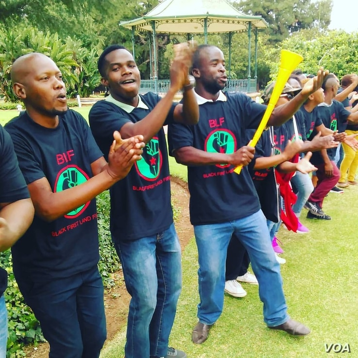A male group of activists are seen during a rally at a Pretoria part, demanding faster action on land ressitution. (A. Powell/VOA)