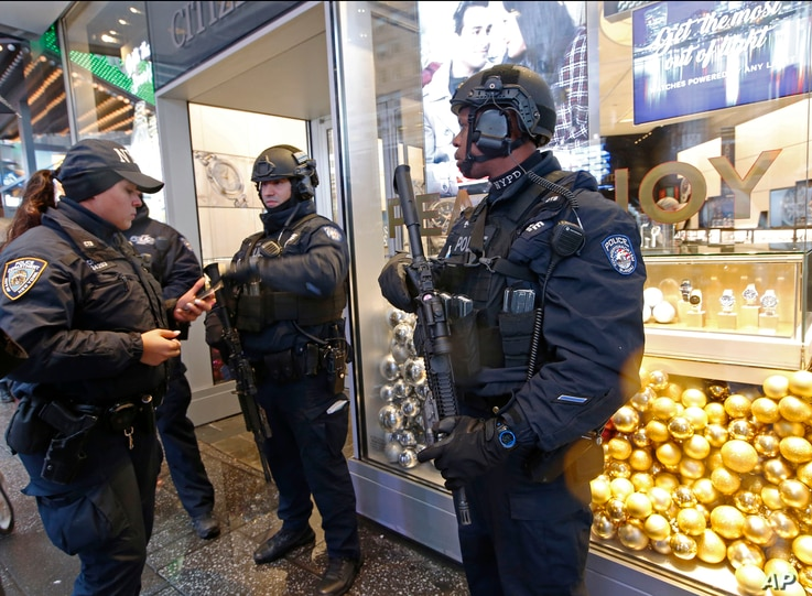 Counterterrorism officers stand in front of a watch store in Times Square, Dec. 29, 2016, in New York, as they take shelter from the rain.