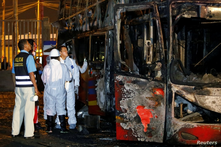 Peruvian police and investigators work next to a burnt bus on a street in Lima, Peru, March 31, 2019.