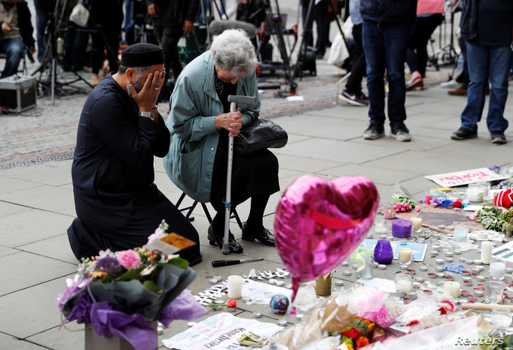 A Jewish woman named Renee Rachel Black and a Muslim man named Sadiq Patel react next to floral tributes in St Ann's Square in Manchester, May 24, 2017.