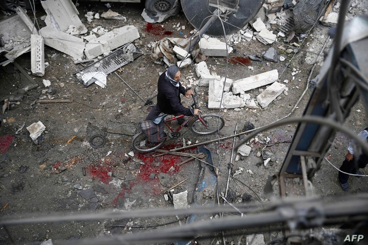 A Syrian man walks with a bicycle amid the rubble of destroyed buildings following a reported air strike by Syrian government forces in the rebel-held area of Douma, east of the capital Damascus, on Oct. 29, 2015.