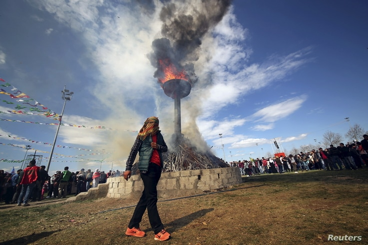 A masked demonstrator walks around a bonfire during a gathering to celebrate the spring festival of Newroz in the Kurdish-dominated southeastern city of Diyarbakir, Turkey, March 21, 2016.