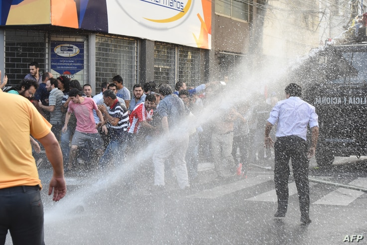 Police crack down with water cannons on a protest against the approval of a constitutional amendment for presidential reelection, outside Congress in Asuncion, March 31, 2017.
