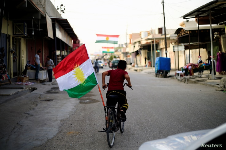 A boy rides a bicycle with the flag of Kurdistan in Tuz Khurmato, Iraq Sept. 24, 2017.