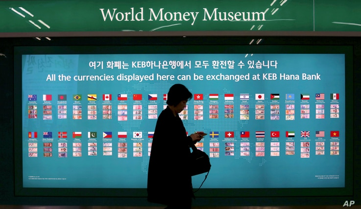 South Korea EconomyFILE - A woman walks by a board displaying various banknotes issued in the world at a subway station in Seoul, South Korea, Oct. 19, 2017. According to estimates, Chinese sanctions over Seoul's deployment of the THAAD missile defen...