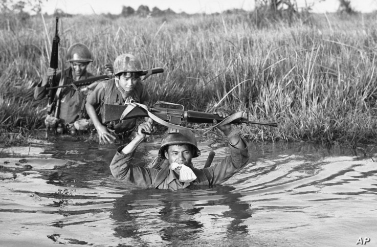 FILE - A South Vietnamese soldier holds his personal belongings in a plastic bag between his teeth as his unit crosses a muddy Mekong Delta stream in Vietnam near the Cambodian border, March 11, 1972. His unit was charged with stemming Communist infi...