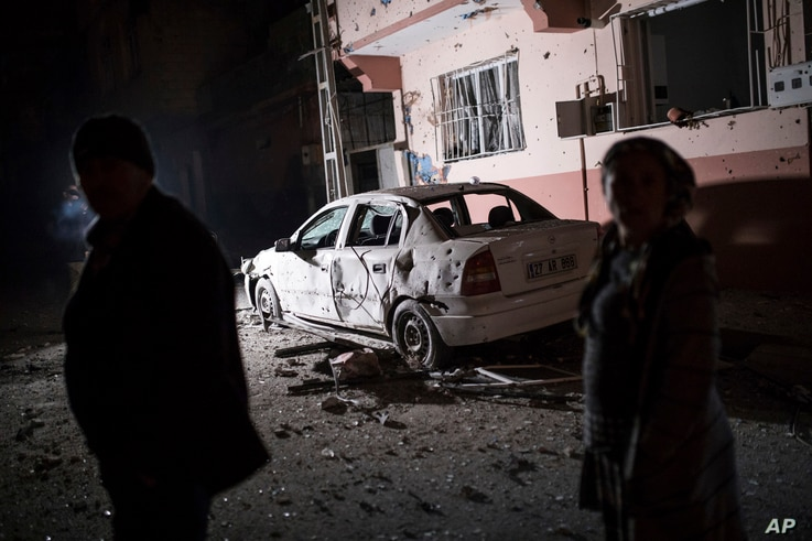 People look at the damage caused by a rocket fired by suspected Syrian Kurdish fighters from Syria, across the border, into the town of Kilis, Turkey, early Jan. 21, 2018. According to the local governor four rockets struck the town, hitting two hous...