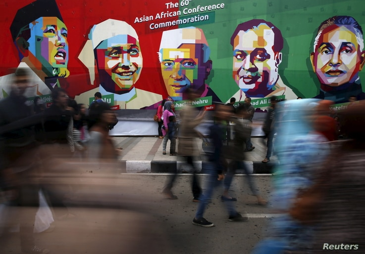 People walk in front a poster of prominent attendees of the 1955 Asian-African Conference on Asia Afrika street in Bandung, Indonesia, April 24, 2015. Leaders of Asian and African nations attended a commemoration ceremony on Friday marking 60 years s...