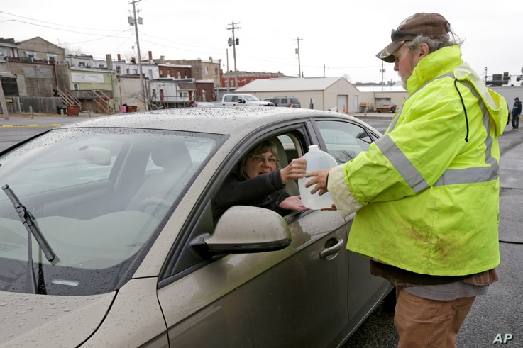 Jeff Vonder, right, an employee of Omaha's Municipal Utilities District, hands Kim O'Connor of Pacific Junction, Iowa, a jug of water he had filled from MUD's emergency water supply tanker, in Glenwood, Iowa, April 3, 2019.
