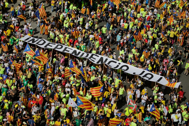 People hold a banner reading 'Independence now' as they gather for a rally to show support for a Catalan independent nation and the right to vote in a controversial referendum that has been banned by Spain, Sept. 11, 2017.