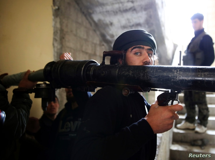 A Free Syrian Army fighter prepares to fire a B-10 recoilless gun in the Haresta neighborhood of Damascus, Feb. 7, 2013.