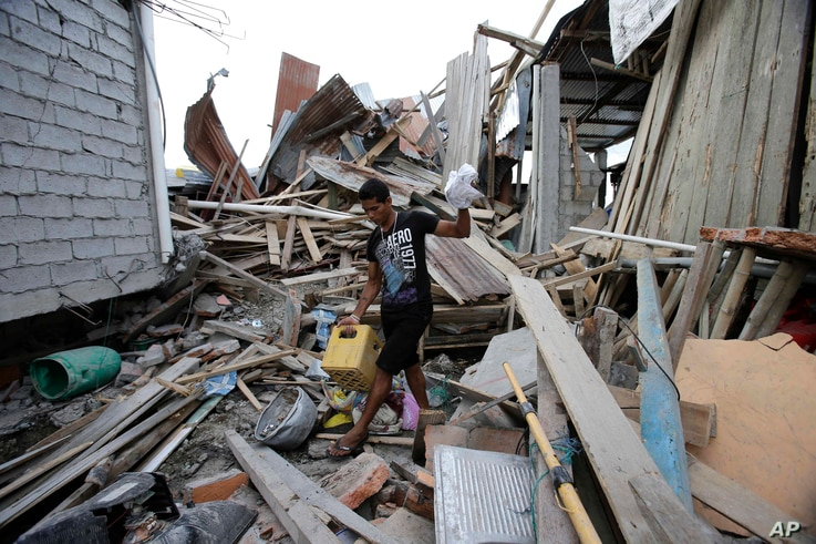 A man, whose wife and unborn son were killed during a 7.8-magnitude earthquake, recovers belongings from his collapsed home, in La Chorrera, Ecuador, April 18, 2016.