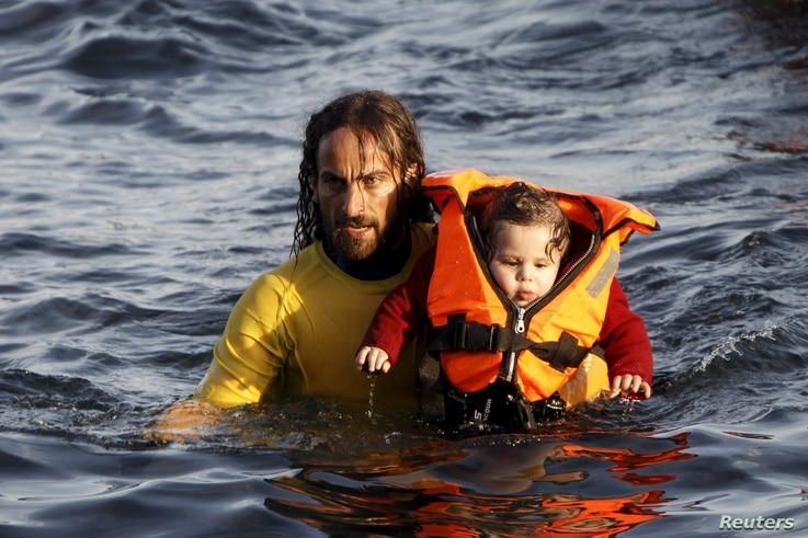 A volunteer lifeguard holds a baby as a half-sunken catamaran carrying around 150 refugees, most of them Syrians, arrives after crossing part of the Aegean sea from Turkey on the Greek island of Lesbos, Oct. 30, 2015.
