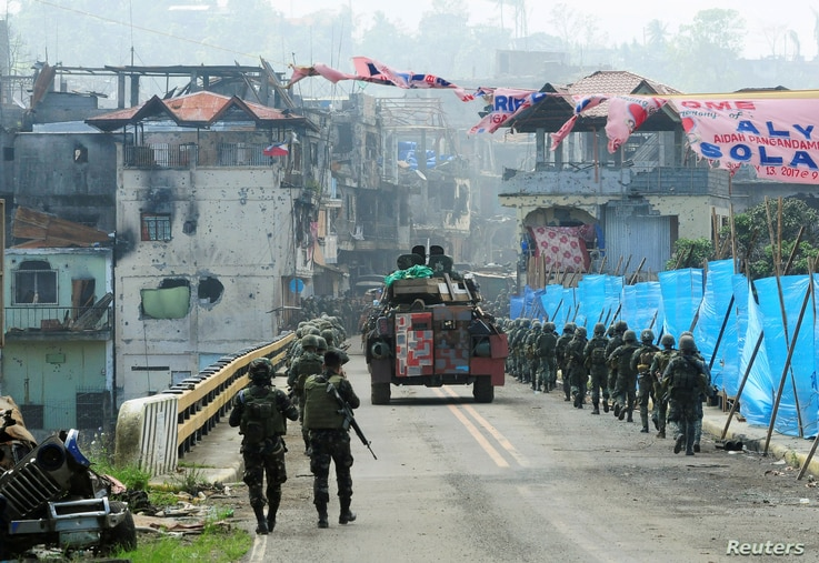 An Armoured Personnel Carrier (APC) and government troops march towards Mapandi bridge after 100 days of intense fighting between soldiers and insurgents from the Maute group, who have taken over parts of Marawi city, southern Philippines August 30, ...