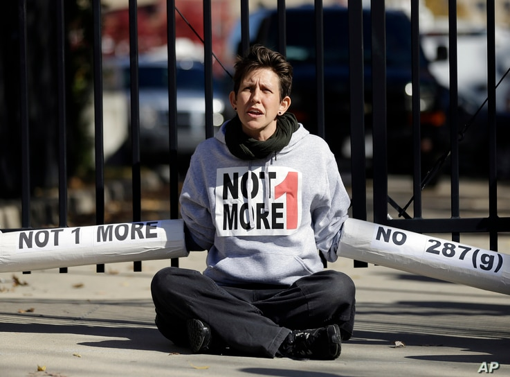 FILE - An Immigration activist, protesting deportations of people who are in the country illegally, blocks the front gate of a building that houses federal immigration authorities in Atlanta.