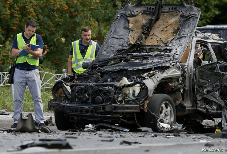 Investigators work at the scene of a car bomb explosion which killed Maxim Shapoval, a high-ranking official involved in military intelligence, in Kiev, Ukraine, June 27, 2017.