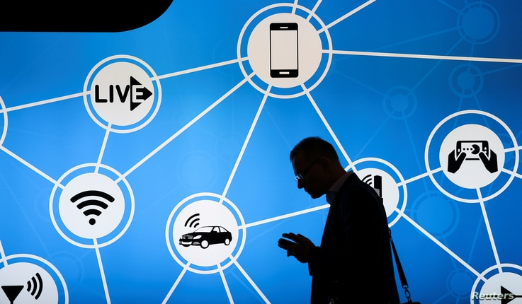 A man looks at his phone in front of a stand at the Mobile World Congress in Barcelona, Spain, showing a variety of devices connected via Wi-Fi and Internet of Things networks, Feb. 28, 2017