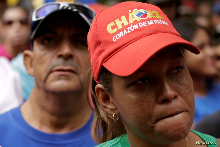 """A supporter of Venezuela's President Nicolas Maduro wears a cap that reads, """"Chavez, heart of my homeland,"""" as she attends a rally against the application of Organization of American States (OAS) democratic charter, in Caracas, Venezuela, June 23, 20..."""