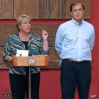 Chilean President Michelle Bachelet (L) delivers a press conference at La Moneda presidential palace in Santiago on 28 Feb 2010, next to a member of the Emergency Committee, a day after a huge 8.8-magnitude earthquake rocked the country.