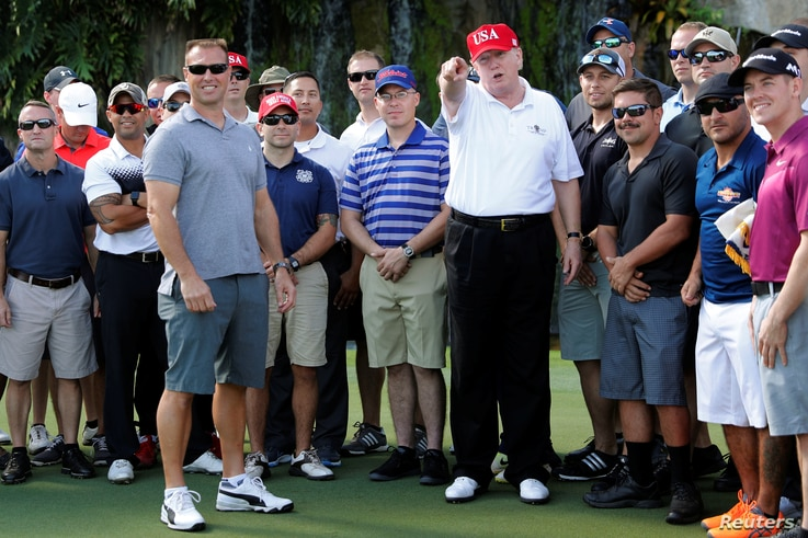 U.S. President Donald Trump stands with U.S. Coast Guard Chief Warrant Officer Gene Gibson (L), commanding officer of the Lake Worth Inlet Station, as Trump plays host to members of the U.S. Coast Guard he invited to play golf at his Trump Internatio...
