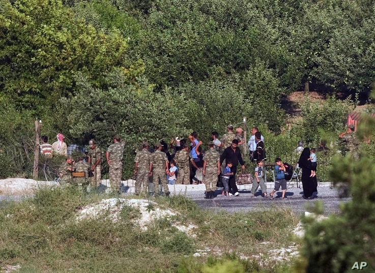 FILE - Newly arrived Syrians enter Turkey as several others wait inside Syria to cross the border near the Turkish village of Guvecci in Hatay province, June 19, 2011. As the border tightened, refugees fortunate enough to reach the frontier started b...
