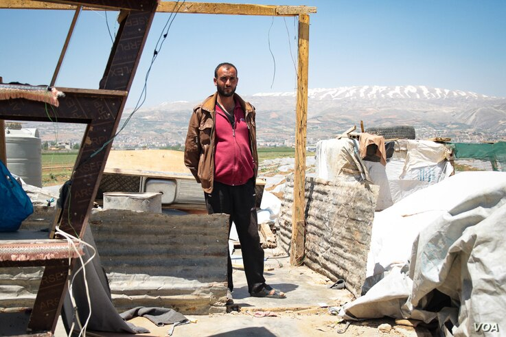 Hussein Muhammed Michel stands among his family's possessions. They have moved the items outside the home in anticipation of a move, but have not yet found a site to move to.