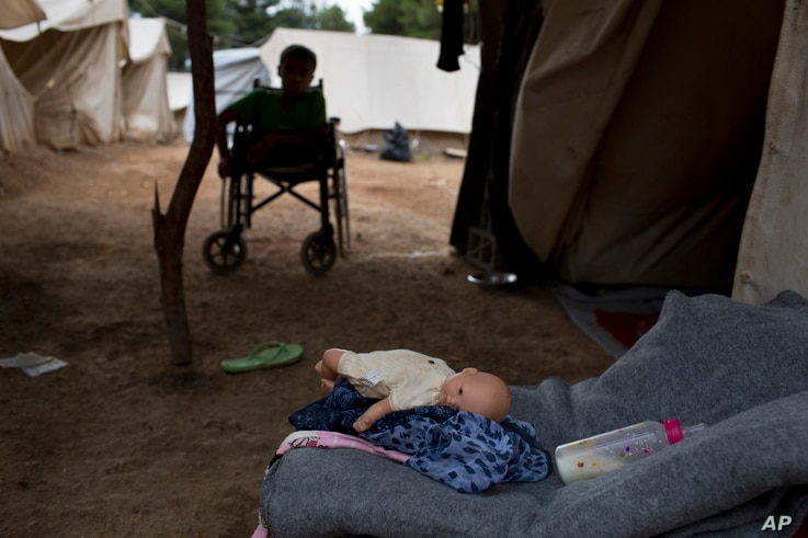 FILE - Fifteen-year-old Ahmed Khalil Isa, a disabled Syrian teenager, sits in his wheelchair outside his family's tent at the Ritsona refugee camp north of Athensm, Greece, Sept. 19, 2016.