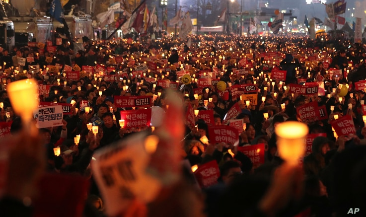 South Korean protesters hold candles during a rally calling for South Korean President Park Geun-hye to step down in Seoul, South Korea, Nov. 19, 2016. For the fourth straight Saturday, masses of South Koreans filled major avenues in downtown Seoul d...