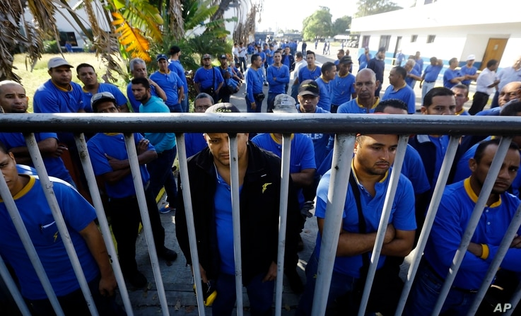 Goodyear workers arrive to find their plant is no longer in operation, in Los Guayabos, Venezuela, Dec. 10, 2018.