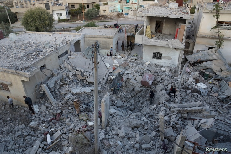 FILE - Residents inspect a damaged site from what activists said were airstrikes carried out by the Russian air force in Nawa city, Deraa, Syria, Nov. 21, 2015.