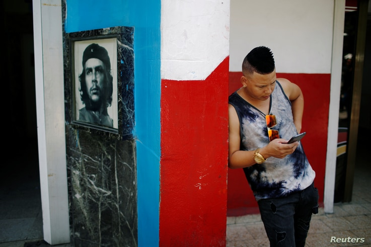 "A young Cuban checks his phone at an internet hotspot next to a picture of late revolutionary hero Ernesto ""Che"" Guevara in Havana,  Aug. 10, 2018."