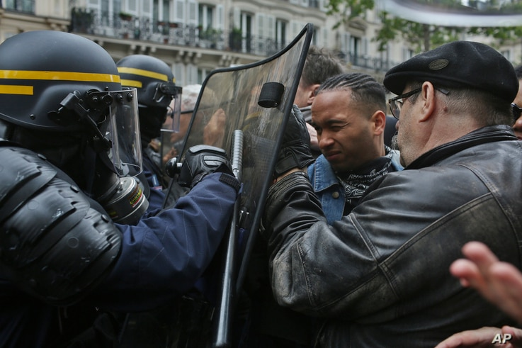 Protesters face riot police officers during a demonstration called by labor unions the day after the French presidential election, May 8, 2017.