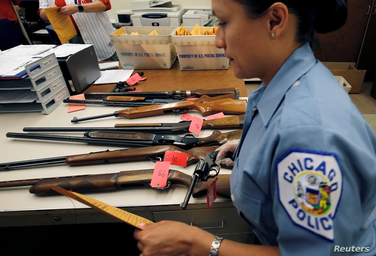 """FILE  A Chicago Police officer prepares to inventory a hand gun turned in from the public as part of the """"Gun Turn-in"""" event where a gift card is given for every firearm turned over to the police in Chicago, Illinois, May 28, 2016."""