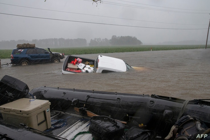 """A pickup is submerged in floodwaters in Lumberton, N.C., Sept. 15, 2018, in the wake of Hurricane Florence. Besides federal and state emergency crews, rescuers were being helped by volunteers from the """"Cajun Navy,"""" civilians equipped with light boats..."""