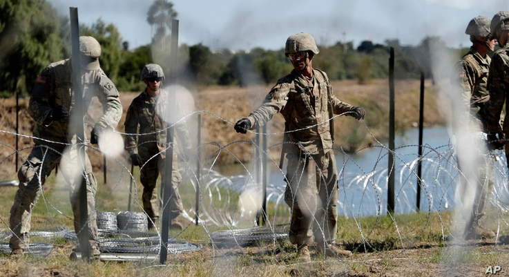 FILE - In this Nov. 16, 2018, photo, members of the U.S. military install multiple tiers of concertina wire along the banks of the Rio Grande near the Juarez-Lincoln Bridge at the U.S.-Mexico border in Laredo, Texas.