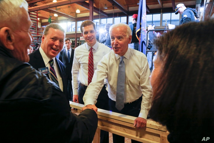 FILE - Conor Lamb, left center, the Democratic candidate for the March 13 special election in Pennsylvania's 18th Congress and former Vice President Joe Biden, center, work a crowd of supporters during a rally at the Carpenter's Training Center in Co...