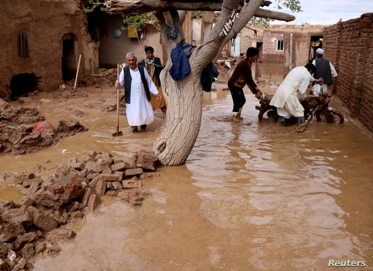 People salvage items from a house destroyed by flood in Enjil district of Herat province, Afghanistan, March 29, 2019.