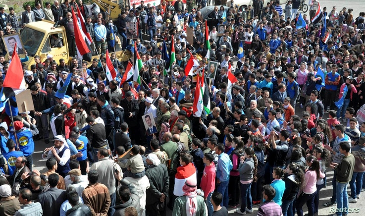 This SANA photo shows supporters of Syrian President Bashar al-Assad attend a rally in Salkha, Sweida, southern Syria, March 4, 2014.