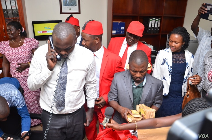 On phone, an officer in the Parliament Accounts office makes frantic calls as members of the opposition storm the office to return $8000 given to them to consult on the Age Limit, Oct. 25, 2017. (Halima Athumani for VOA)
