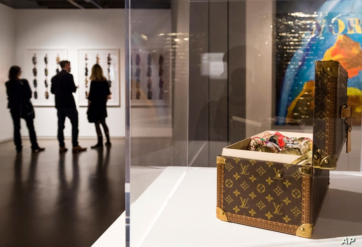 """Visitors stand near an installation by U.S. artist Gregory Green in which a mock bomb is held in a Louis Vuitton vanity case for an exhibition """"Islam, It's Also Our History"""" at the Espace Vanderborght in Brussels, Sept. 19, 2017."""