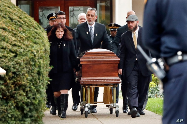 Pittsburgh police stand guard as the casket of Irving Younger, 69, is wheeled from Congregation Rodef Shalom after his funeral on Oct. 31, 2018, in Pittsburgh.