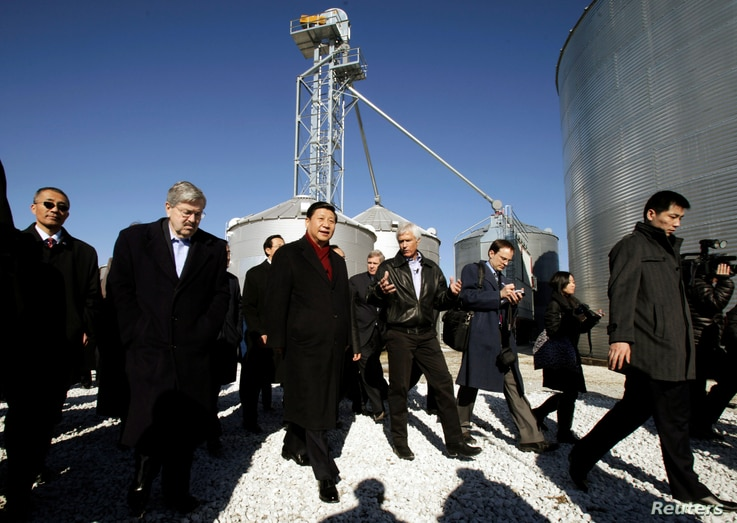 FILE - Chinese Vice President Xi Jinping, third from left, talks with Rick Kimberley, center, and Iowa Governor Terry Branstad, second from left, during a tour of Kimberley's farm, in Maxwell, Iowa, Feb. 16, 2012.