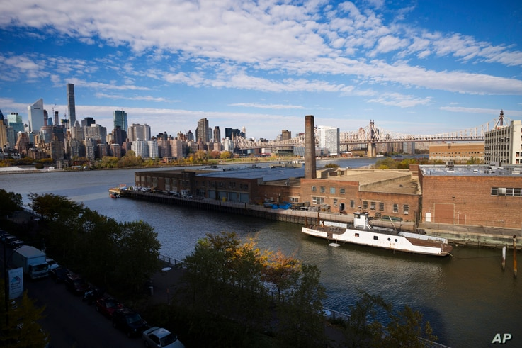 In this Wednesday, Nov. 7, 2018, photo, a rusting ferryboat is docked next to an aging industrial warehouse on Long Island City's Anable Basin in the Queens borough of New York. Across the East River is midtown Manhattan, top left.
