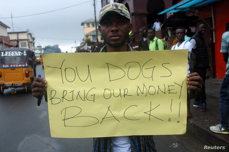 A Liberian demonstrator holds a sign during a protest in Monrovia, Liberia, Sept. 24, 2018.