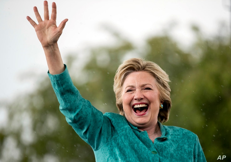 Democratic presidential candidate Hillary Clinton waves as she cuts her speech short because of heavy rain at a rally at C.B. Smith Park in Pembroke Pines, Fla.,  Nov. 5, 2016.