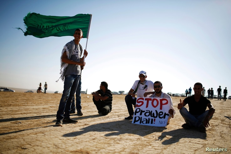 A protester holds a placard as another holds an Islamic movement flag during a demonstration to show their solidarity with Bedouin citizens, near the Bedouin town of Rahat in southern Israel August 1, 2013. Hundreds demonstrated against an Israeli ca...